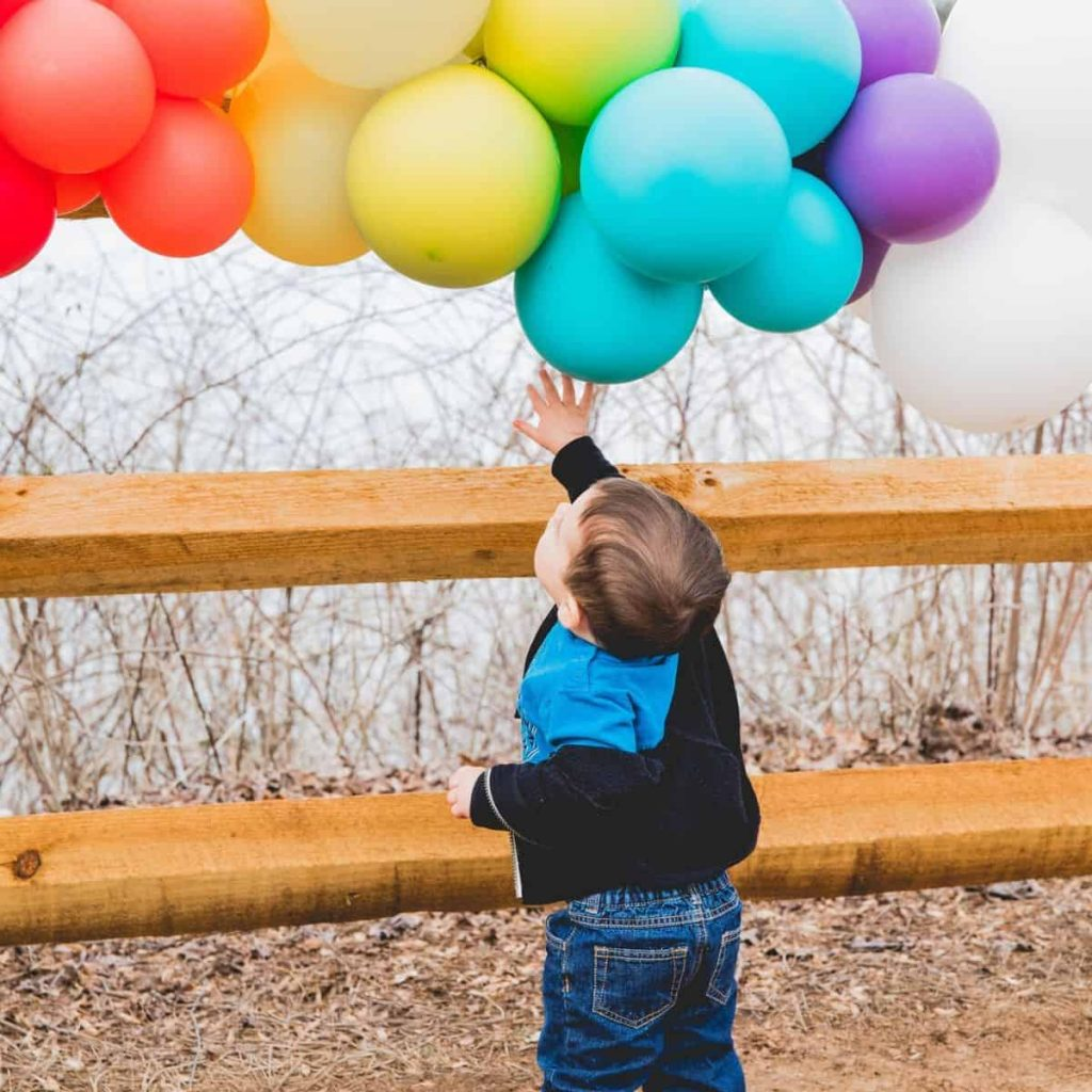 baby playing with rainbow balloons