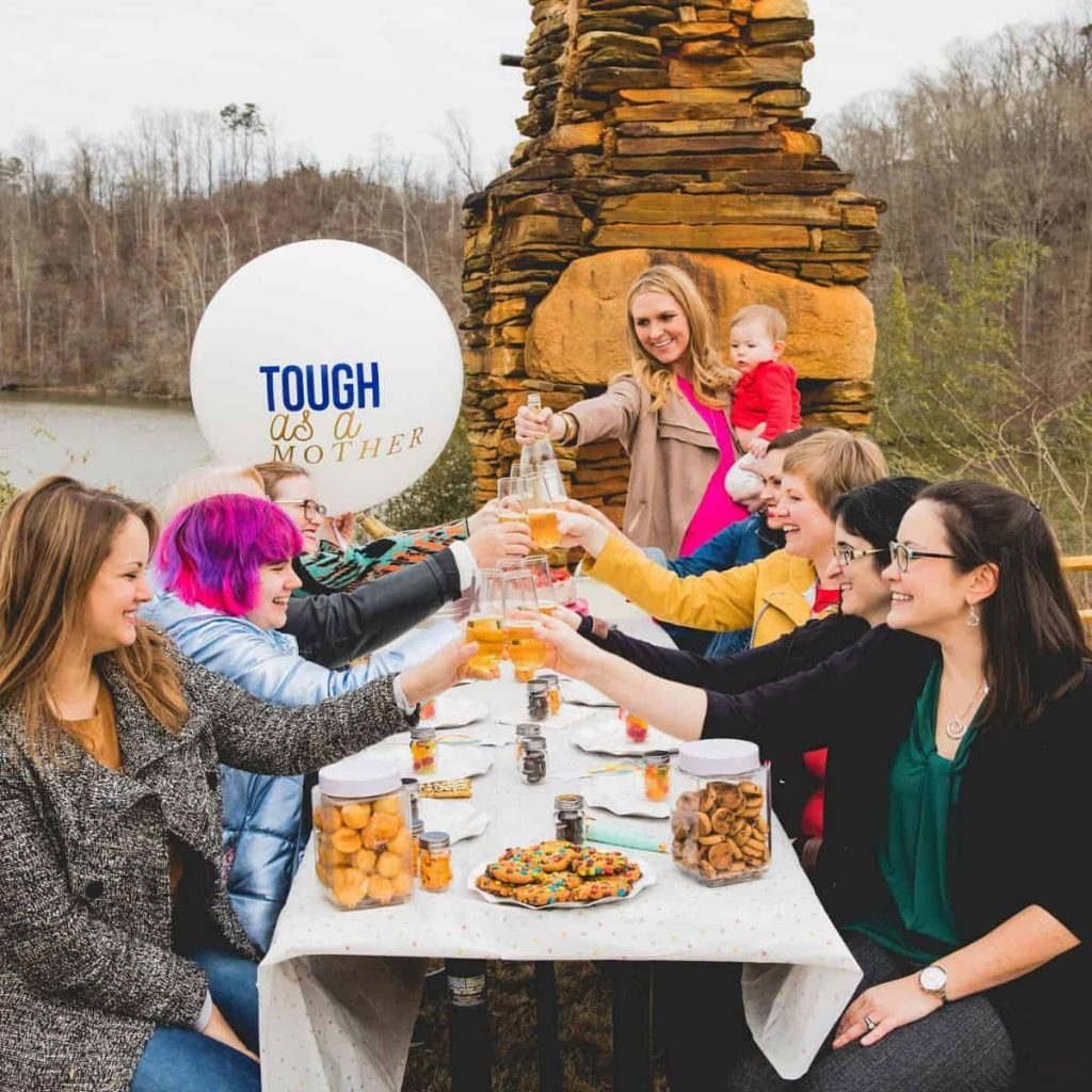 group-of-women-around-table-with-one-holding-a-baby-and-a-balloon-that-says-tough-as-a-mother