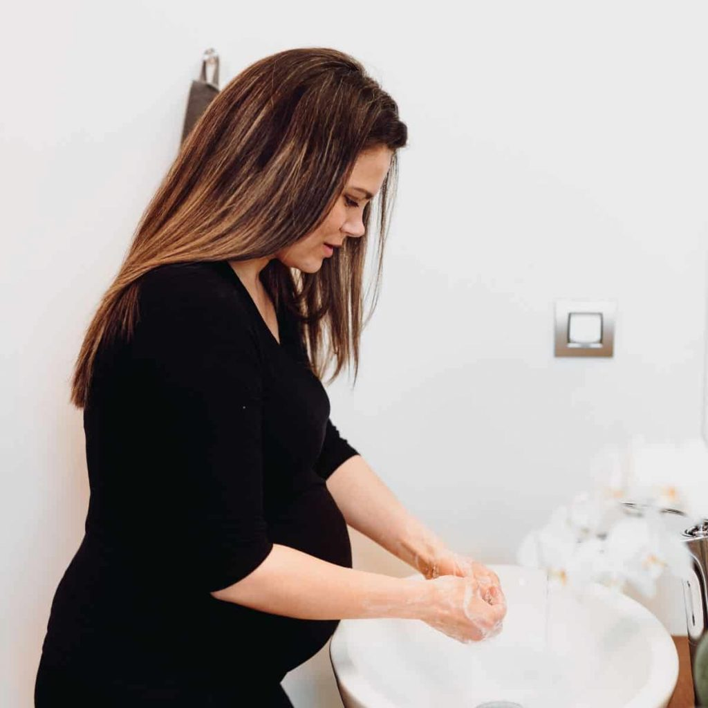 pregnant woman washing her hands with soap and warm water