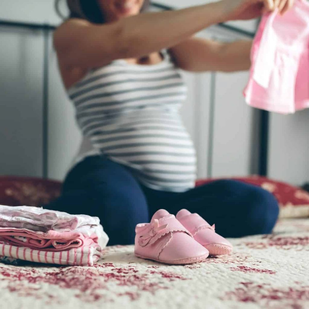 pregnant mom folding clothes getting ready for baby