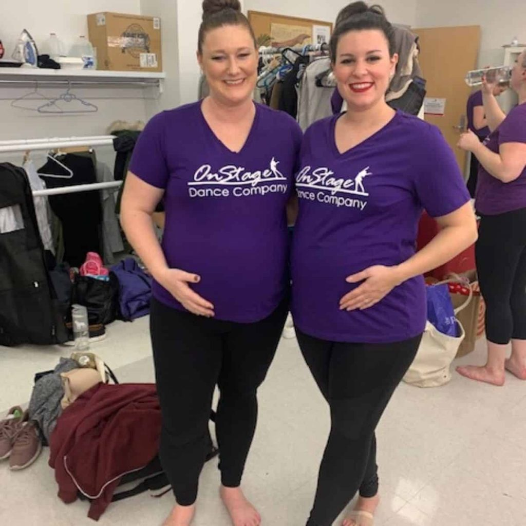 two pregnant women smile in purple shirts that say on stage dance company
