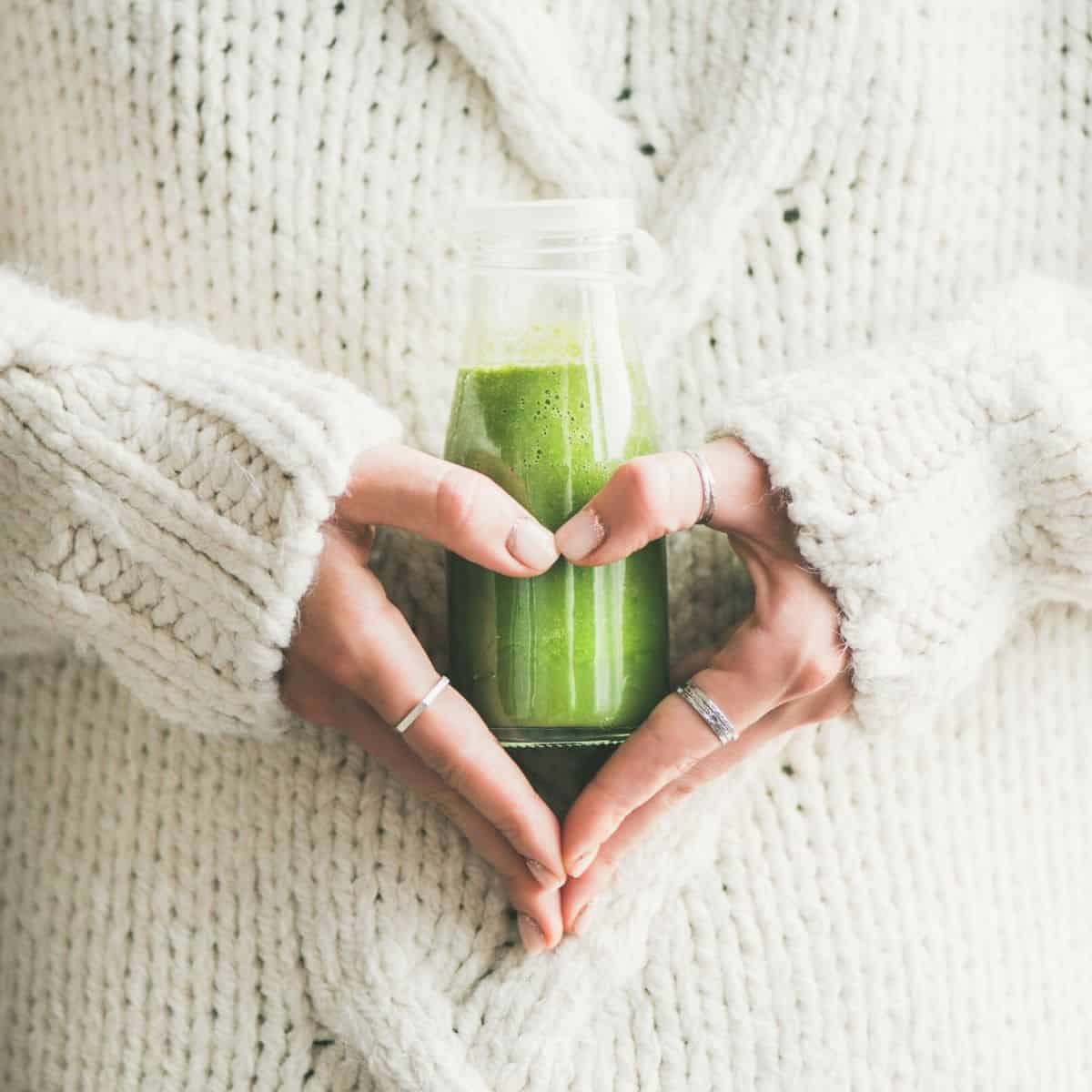 woman holds a green smoothie