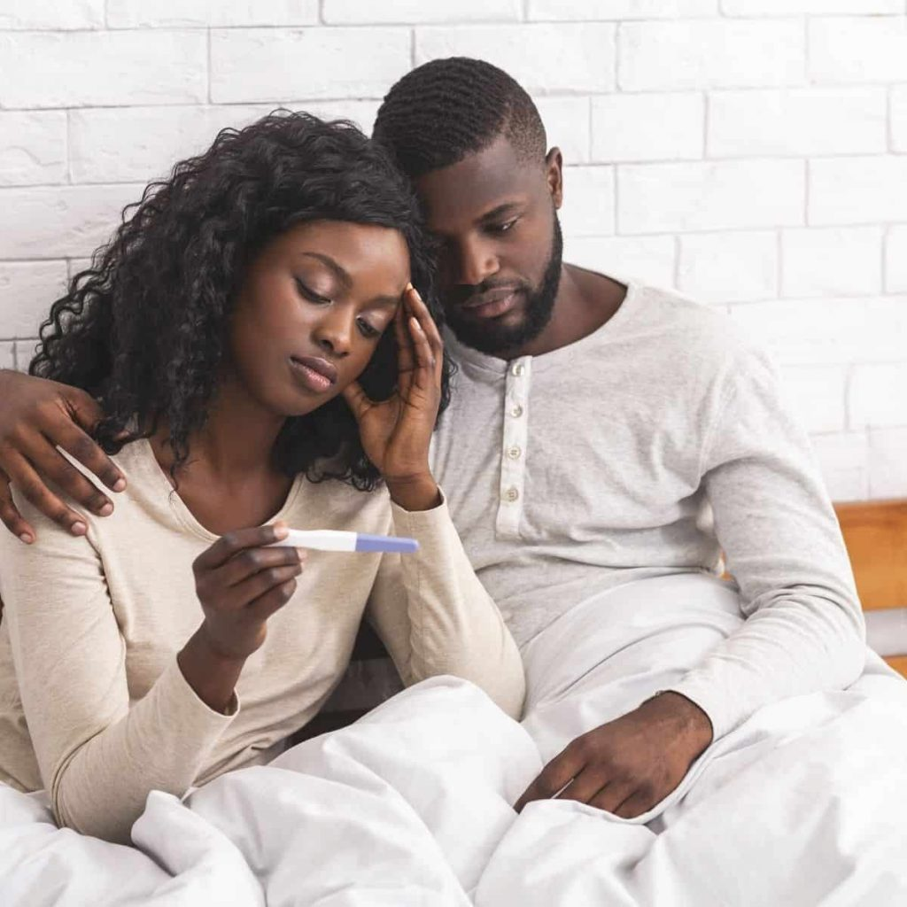two parents looking at the results of a pregnancy test with disappointment