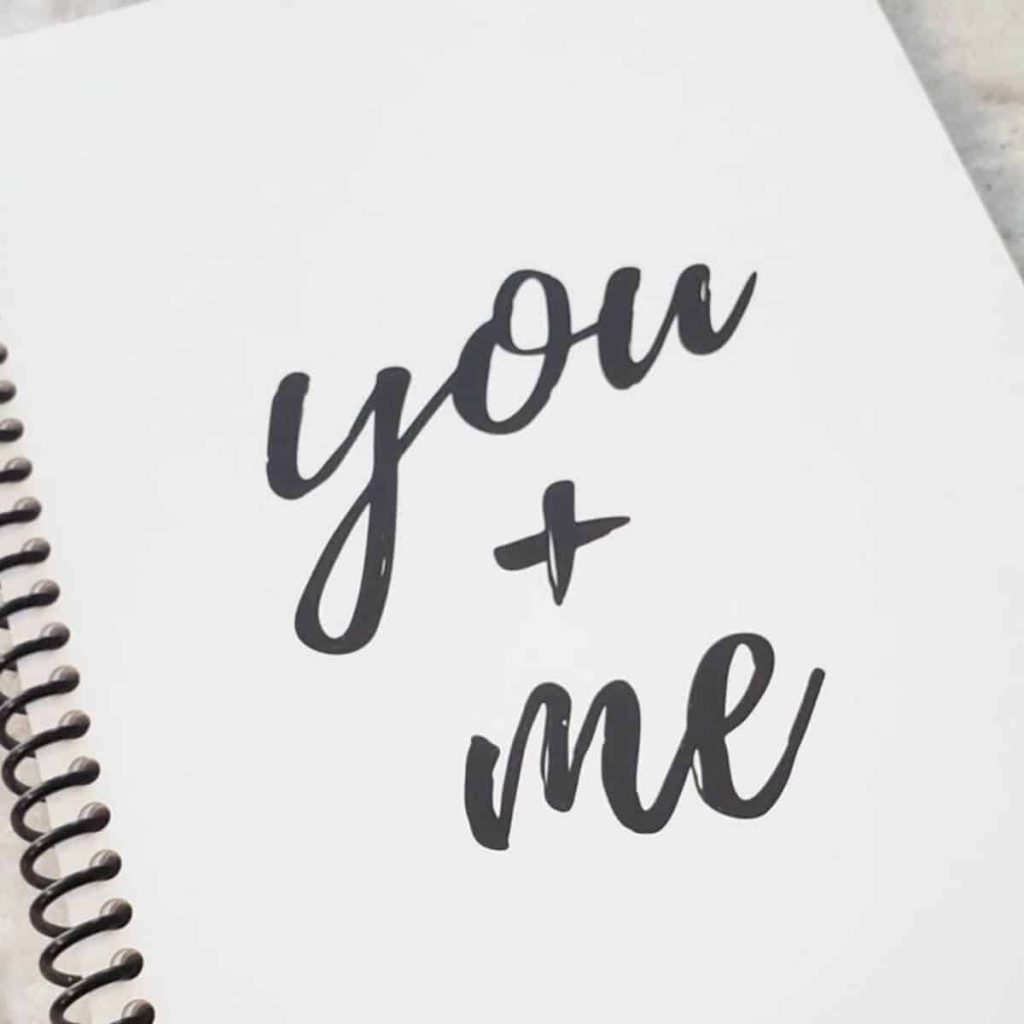Spiral bound white notebook that says you plus me