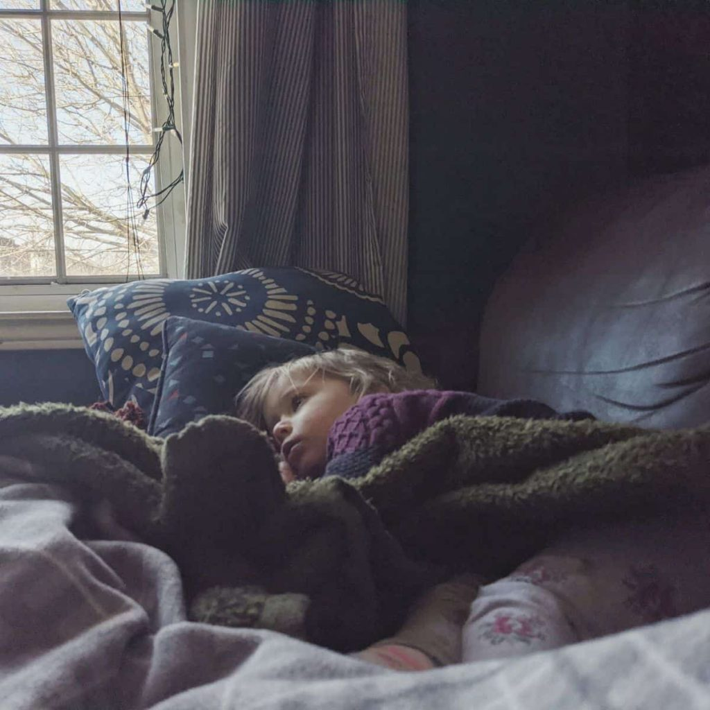child lies on couch with head on pillows