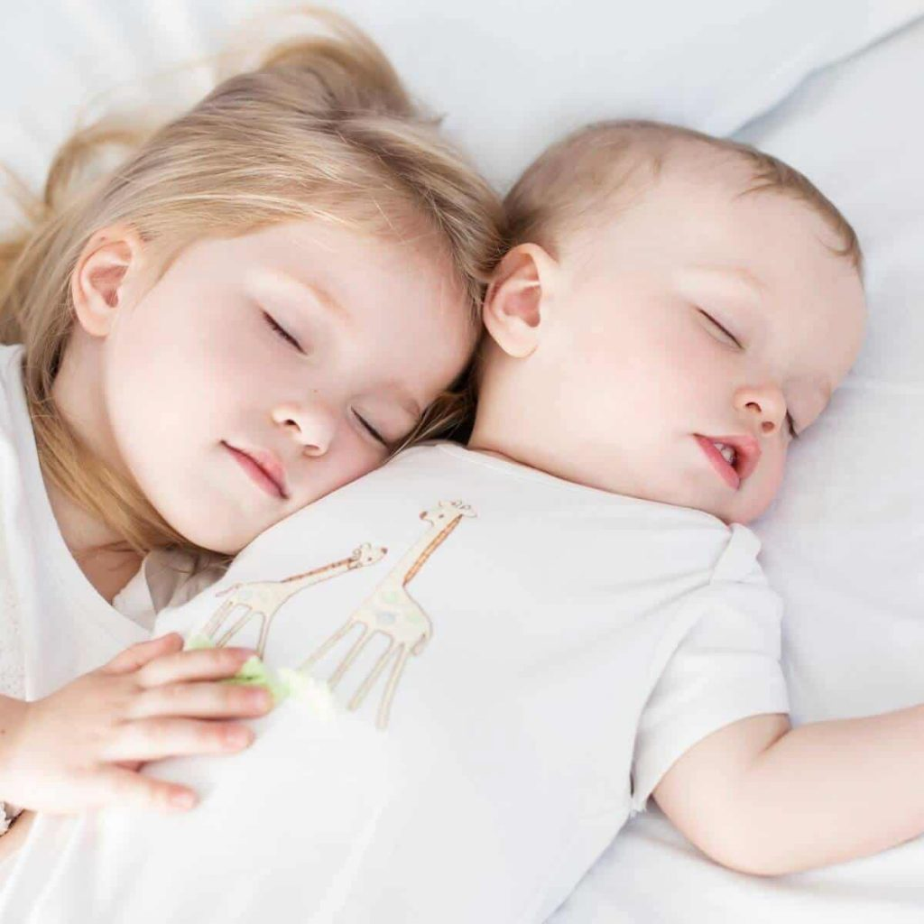 Baby and toddler snuggling on bed in soft white pajamas