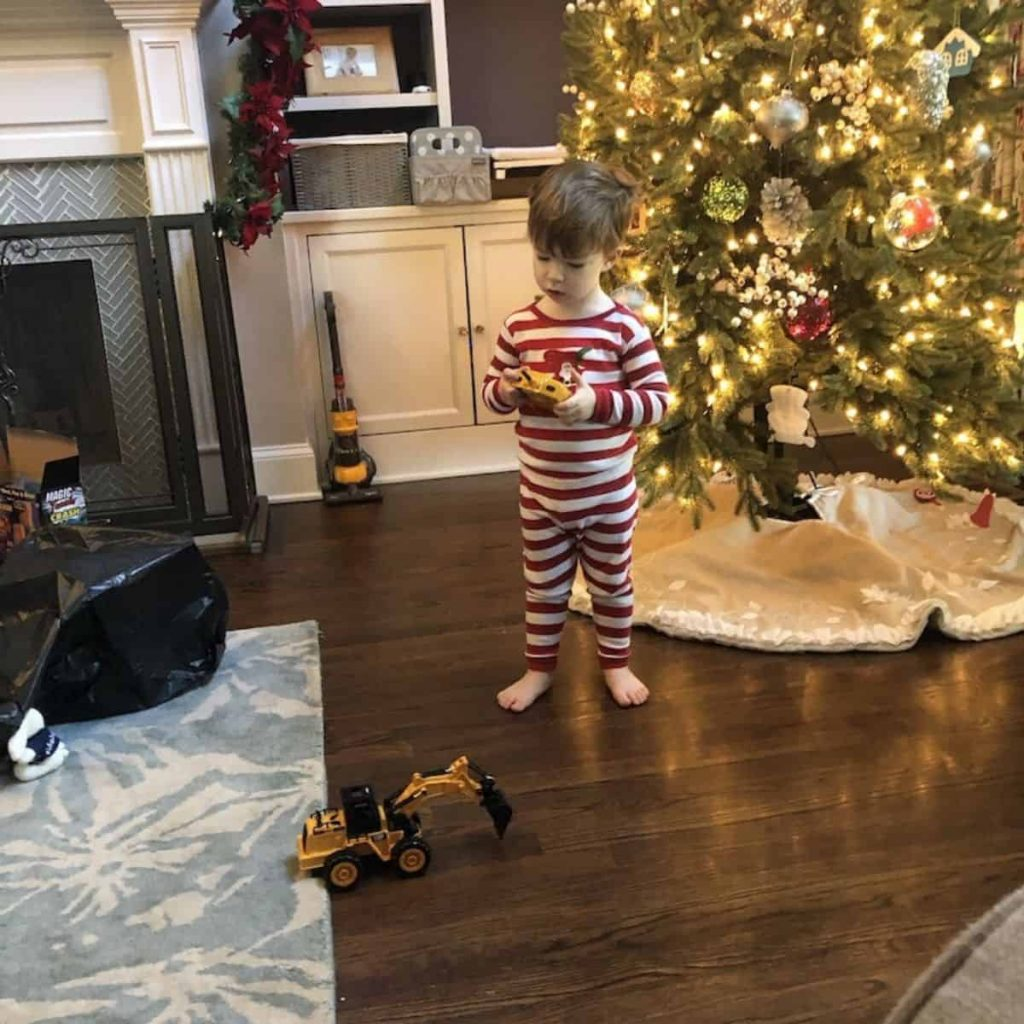 toddler wearing red and white striped leveret pajamas in front of a Christmas tree