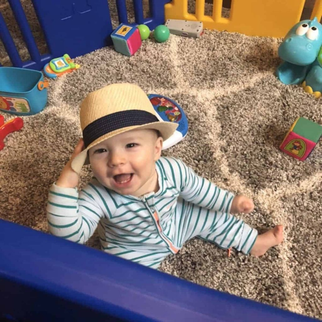 baby wearing blue and white striped bonds wondersuit pajamas sitting in a play pen