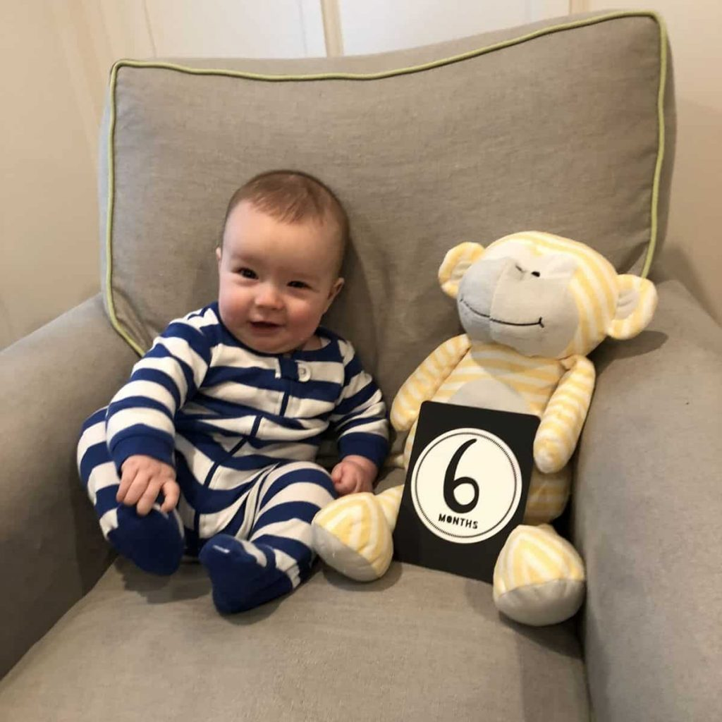 baby wearing a pair of blue and white striped leveret pajamas sitting on a chair with a teddy bear