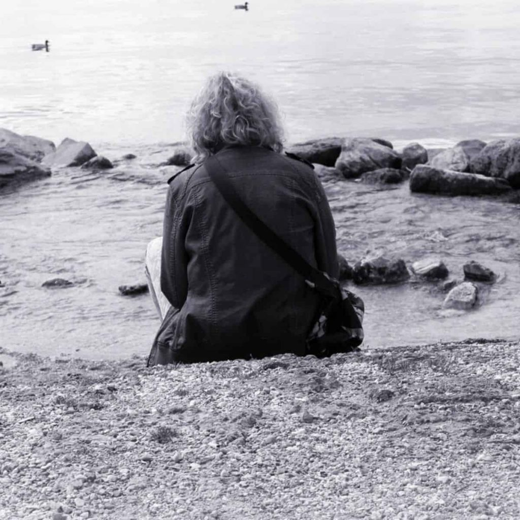 black and white photo of a woman sitting on the beach with her back facing the camera