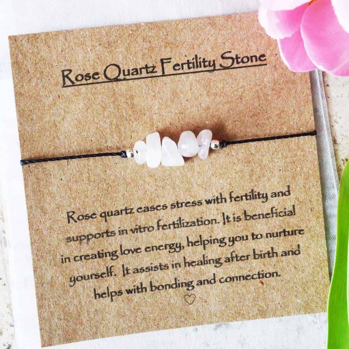 Rose quartz fertility bracelet on brown card with explanation of how the gem helps improve fertility