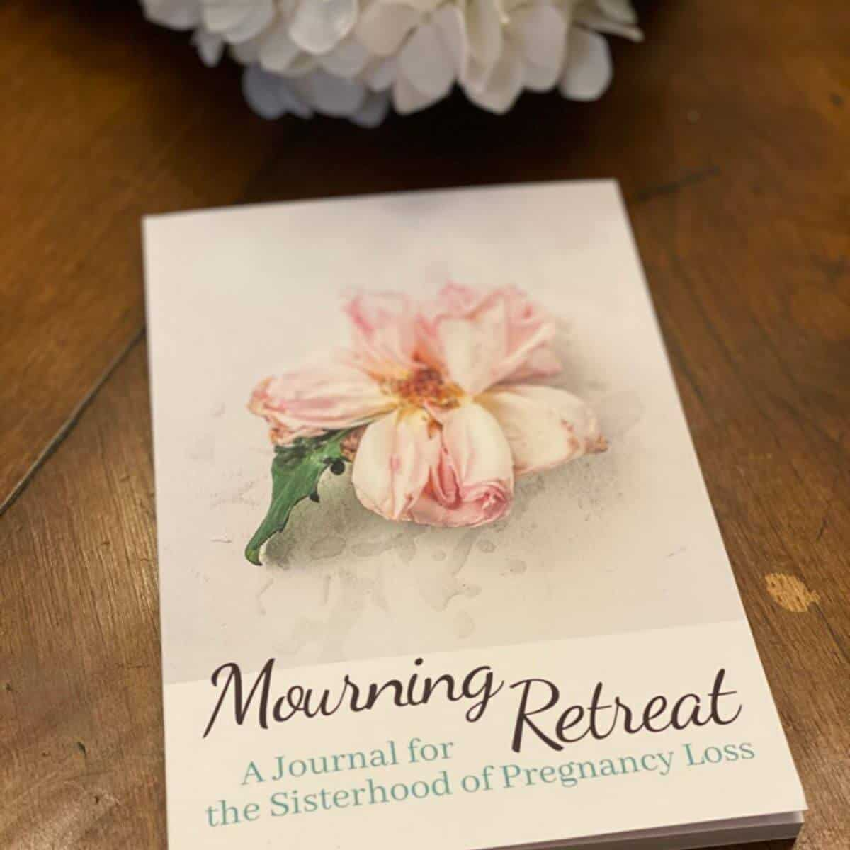 beautiful miscarriage journal called Mourning Retreat a journal for the sisterhood of pregnancy loss lying on a wooden surface with a beautiful flower on the cover