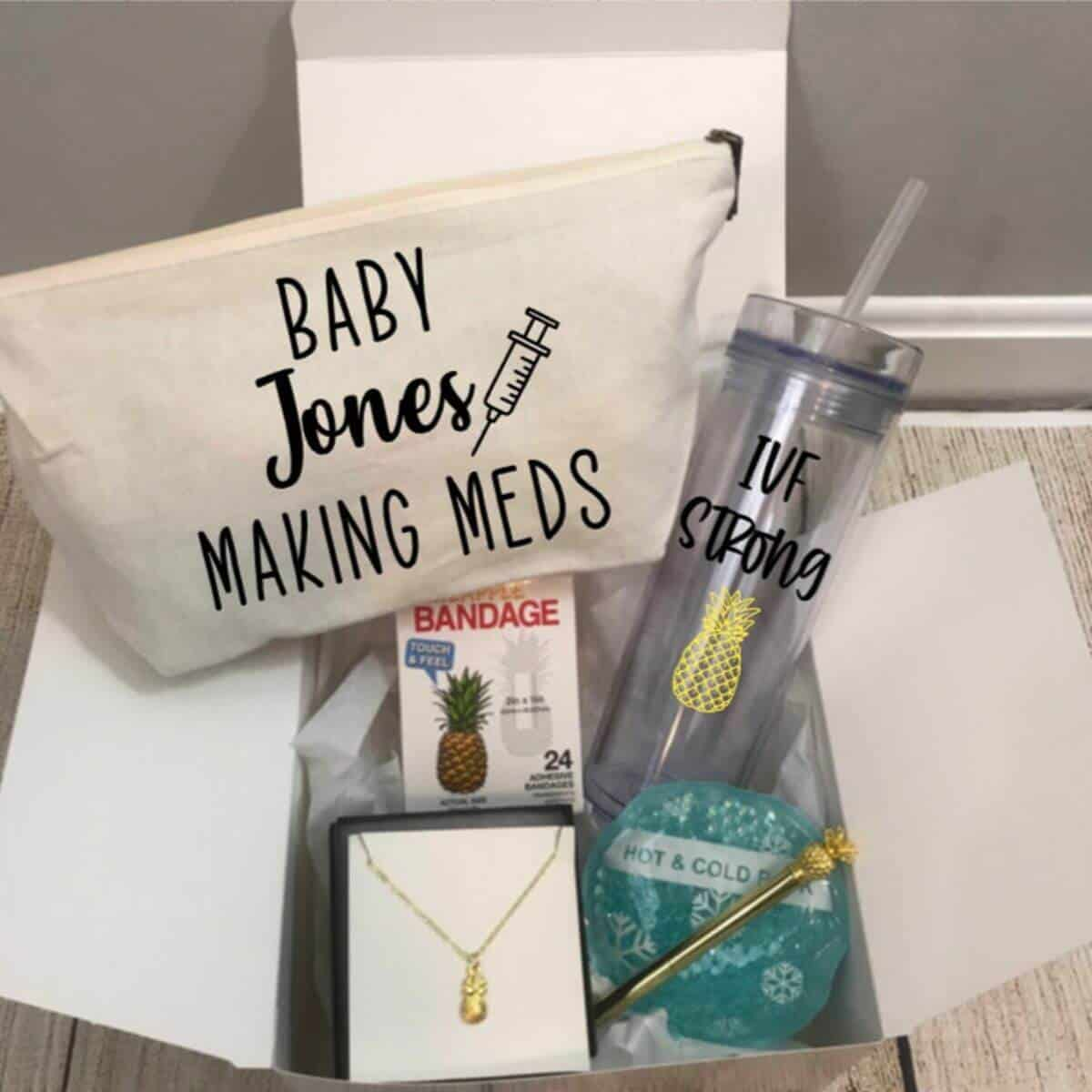 gift box full of gifts for IVF including an IVF medicine bag, a cup, a necklace, and more
