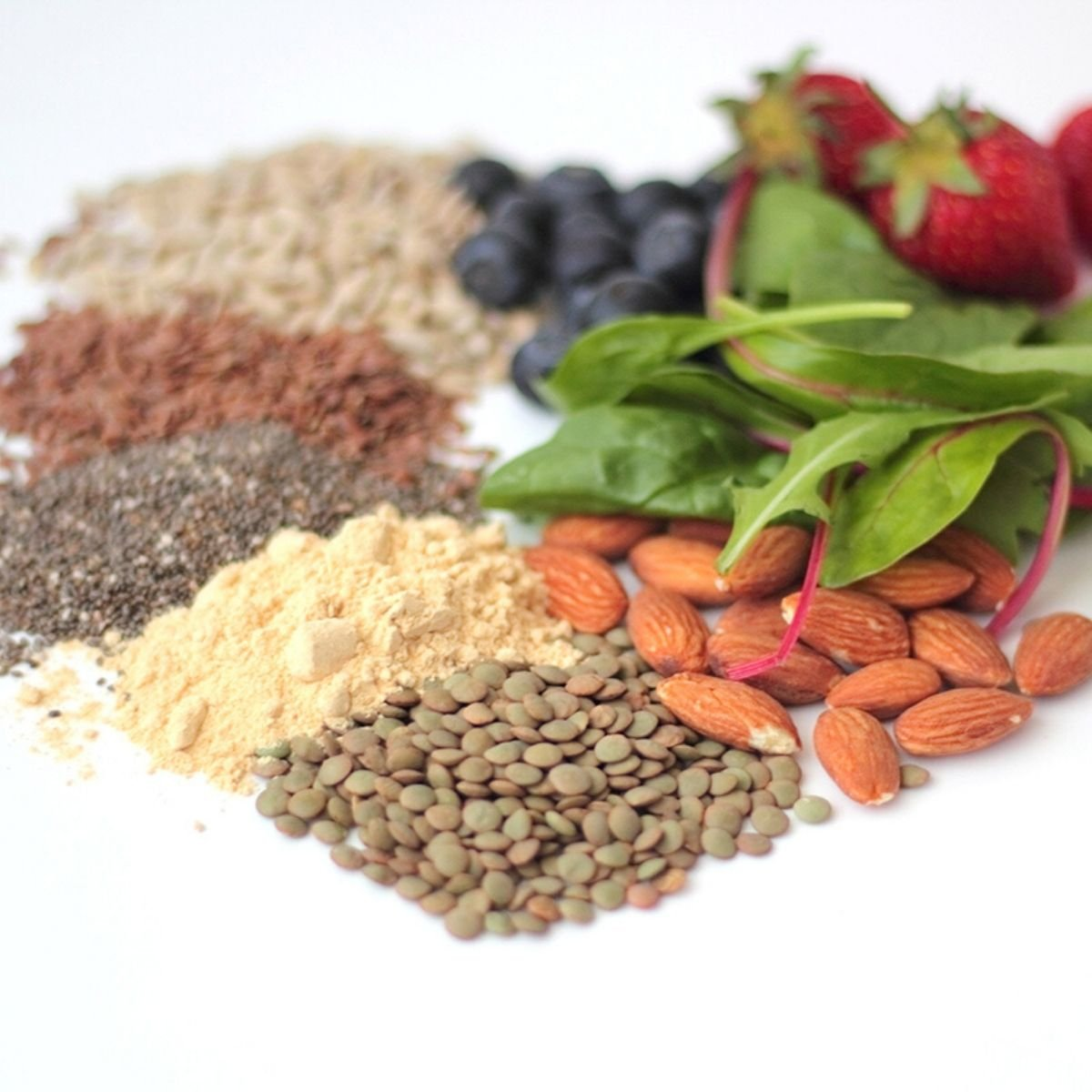 almonds, blueberries, strawberries, spinach, and various spices laid out in the shape of a heart