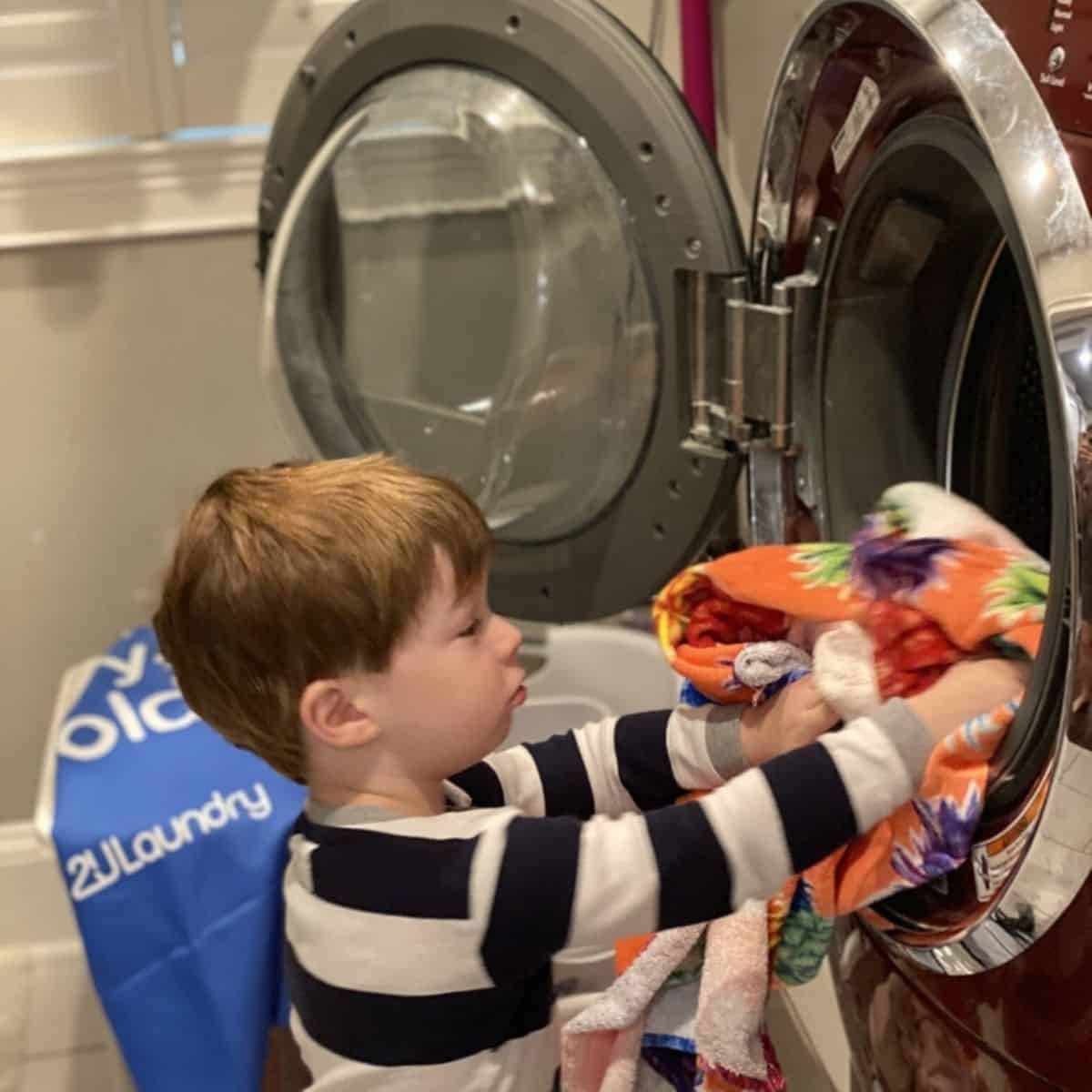 Toddler is pulling clean clothes out of the dryer