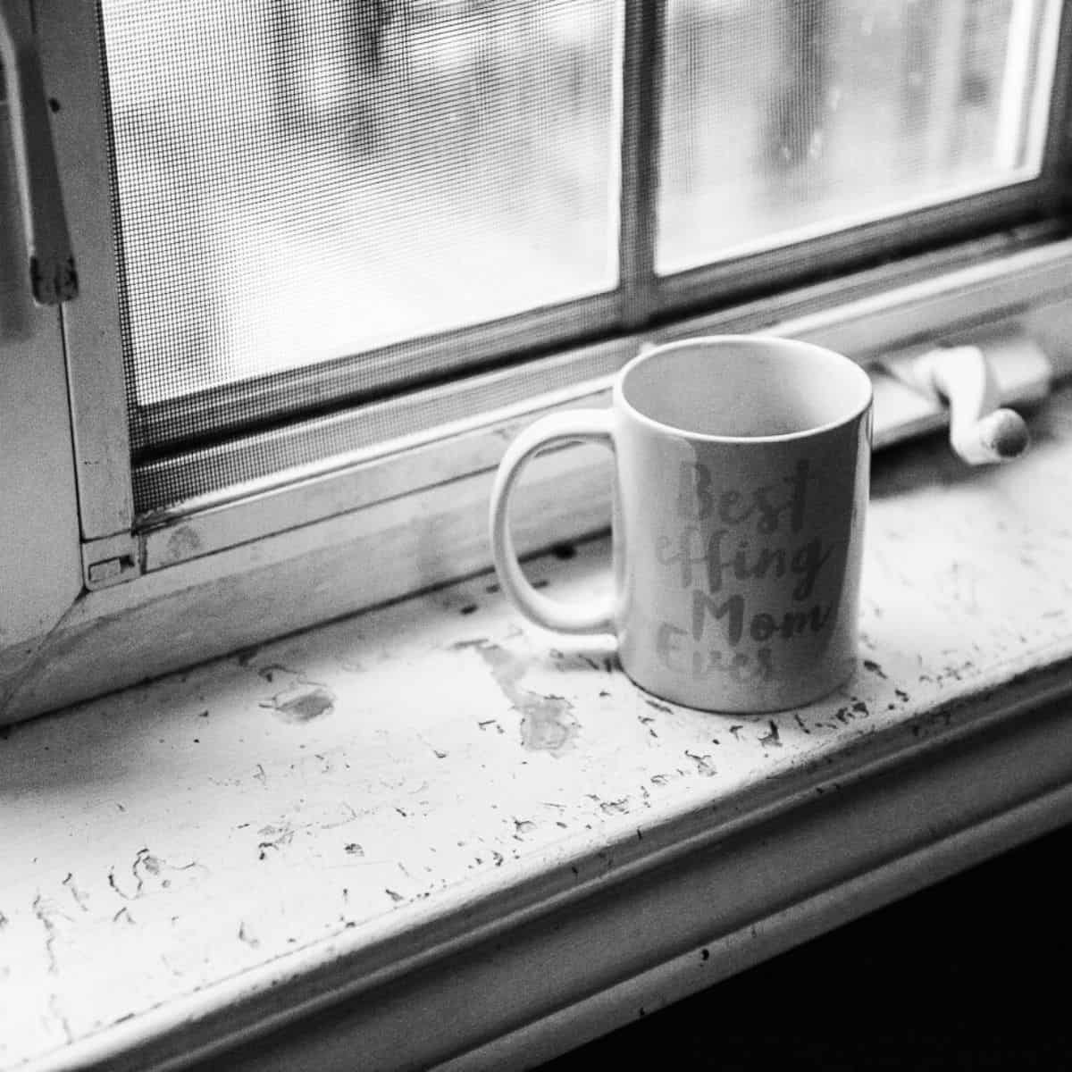 "black and white photo of a mug placed on a window sill that reads ""best effing mom ever"""