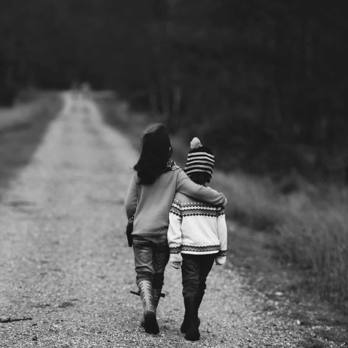 black and white photo of young girl putting her arm around a young boy while they walk down a dirt road