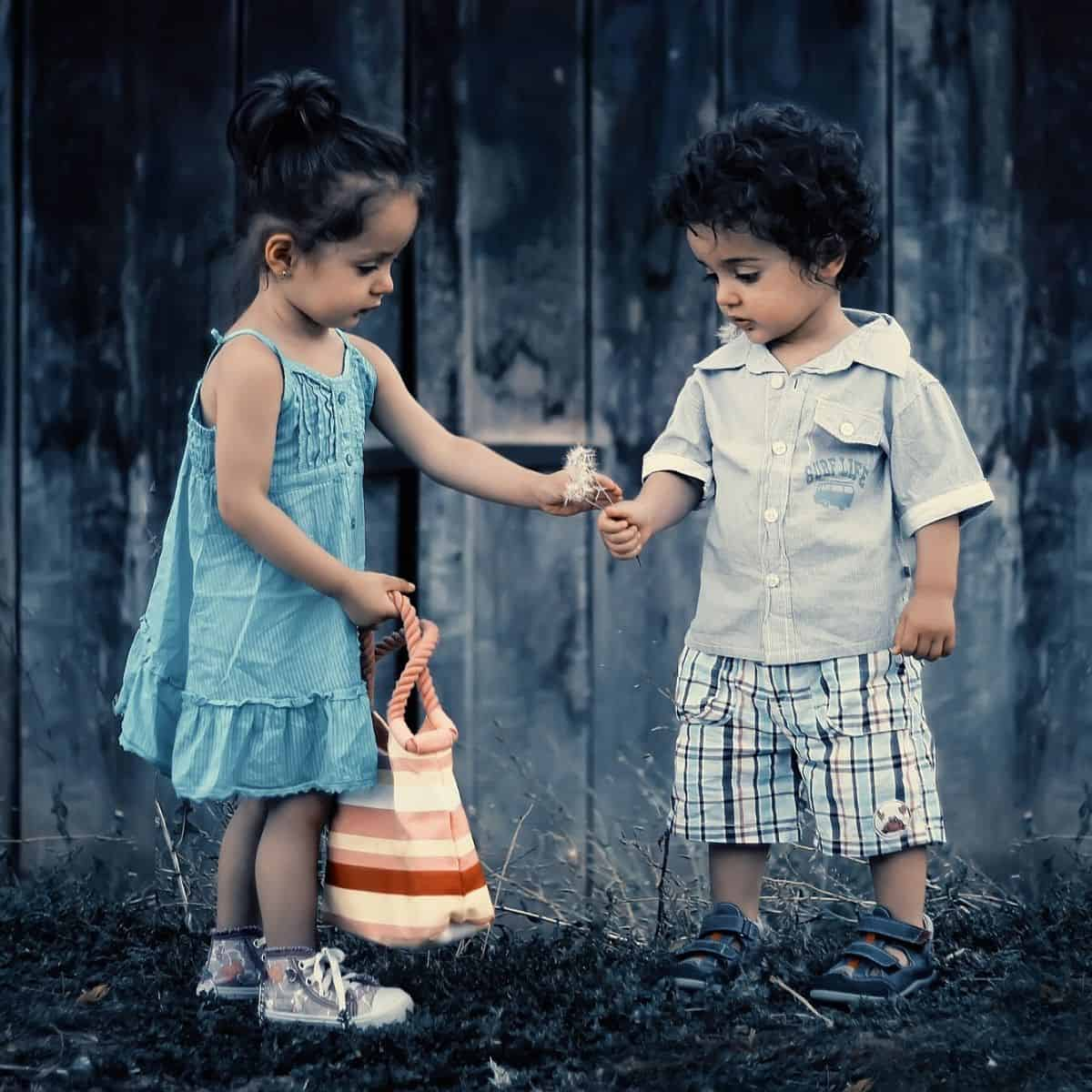 little girl handing dandelions to a little boy, in an act of empathy