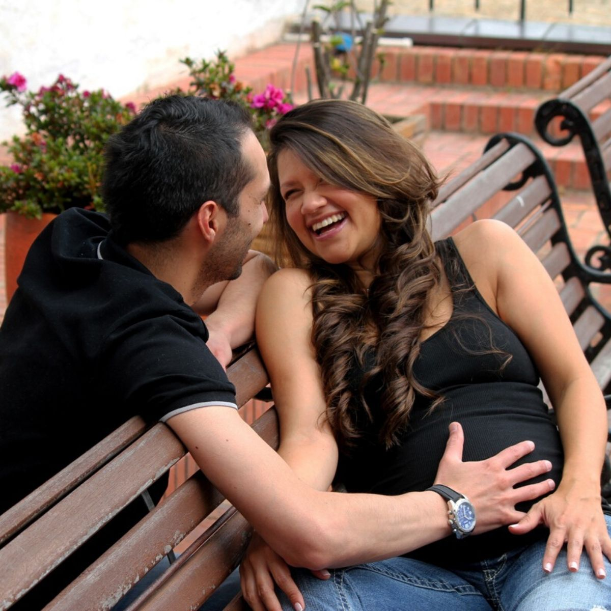 man has his right hand placed on his partner's pregnant stomach while they smile at each other