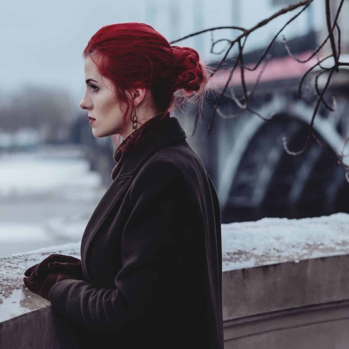 woman with bright red hair appears to be pondering