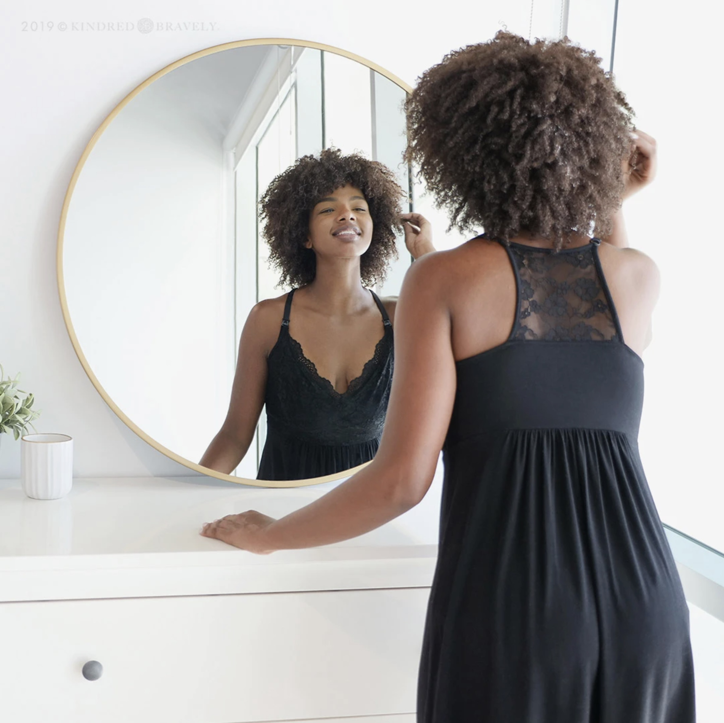 woman looking at her reflection in mirror while wearing black maternity nursing nightgown