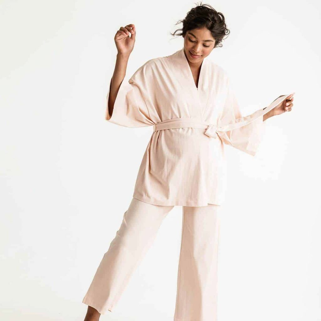 Brunette woman in soft pink nursing pajamas by STORQ
