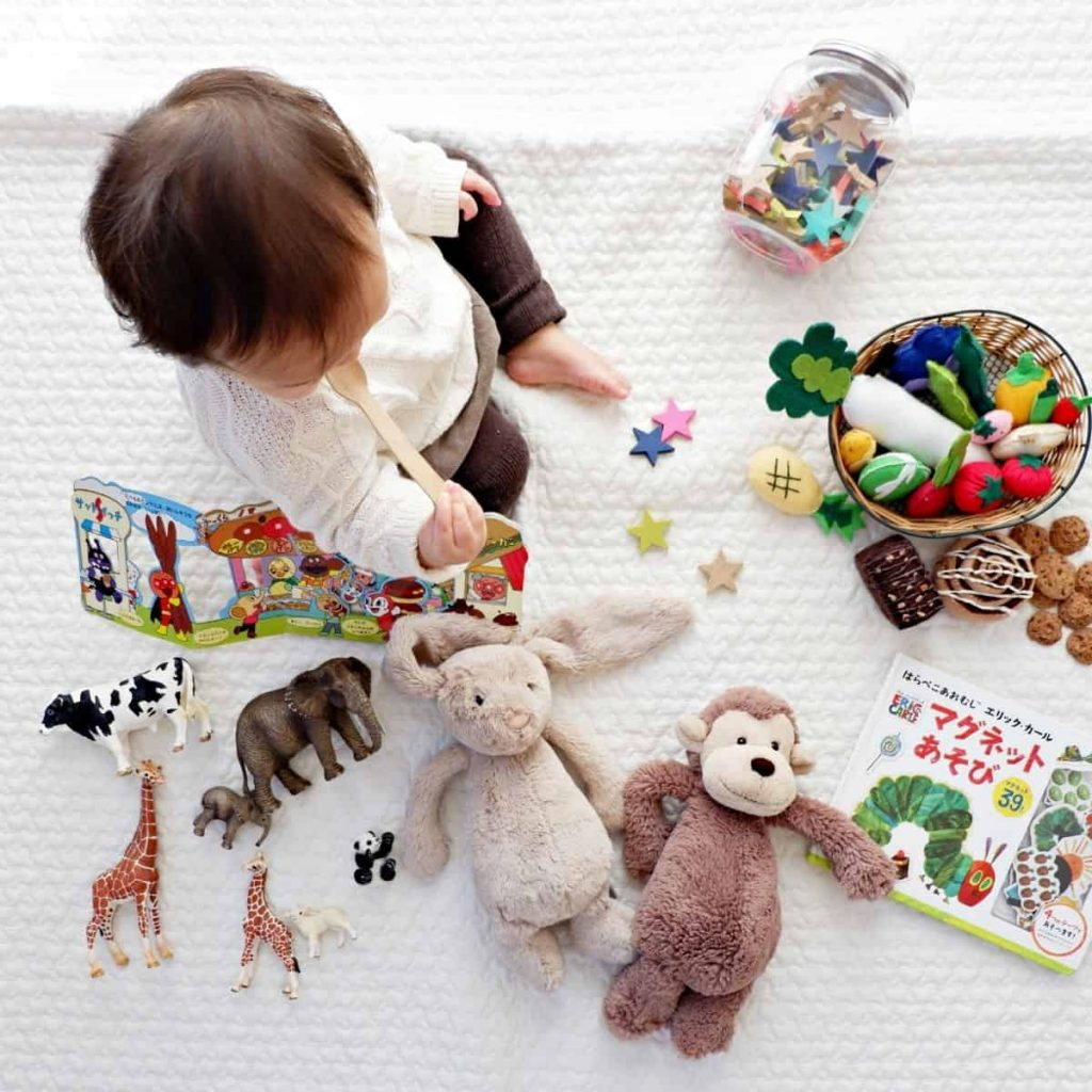 baby surrounded by stuffed animals, plastic toys and developmental toys