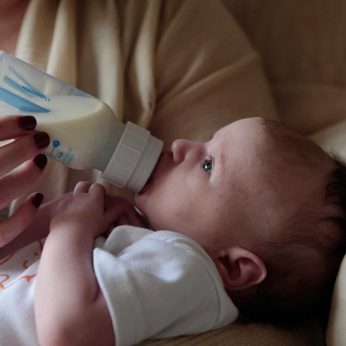 mother is holding baby while the baby is drinking formula from a bottle