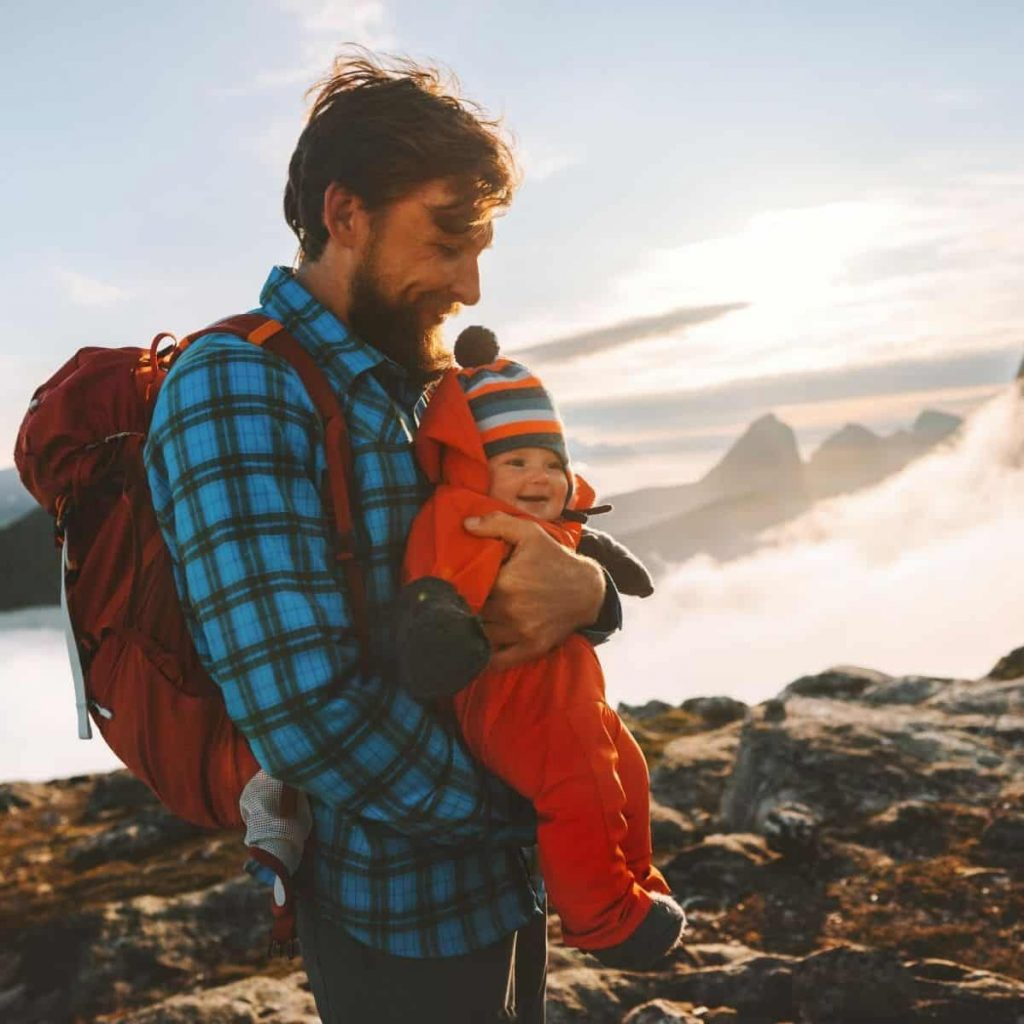 dad wearing a diaper backpack and holding baby while vacationing in the mountains