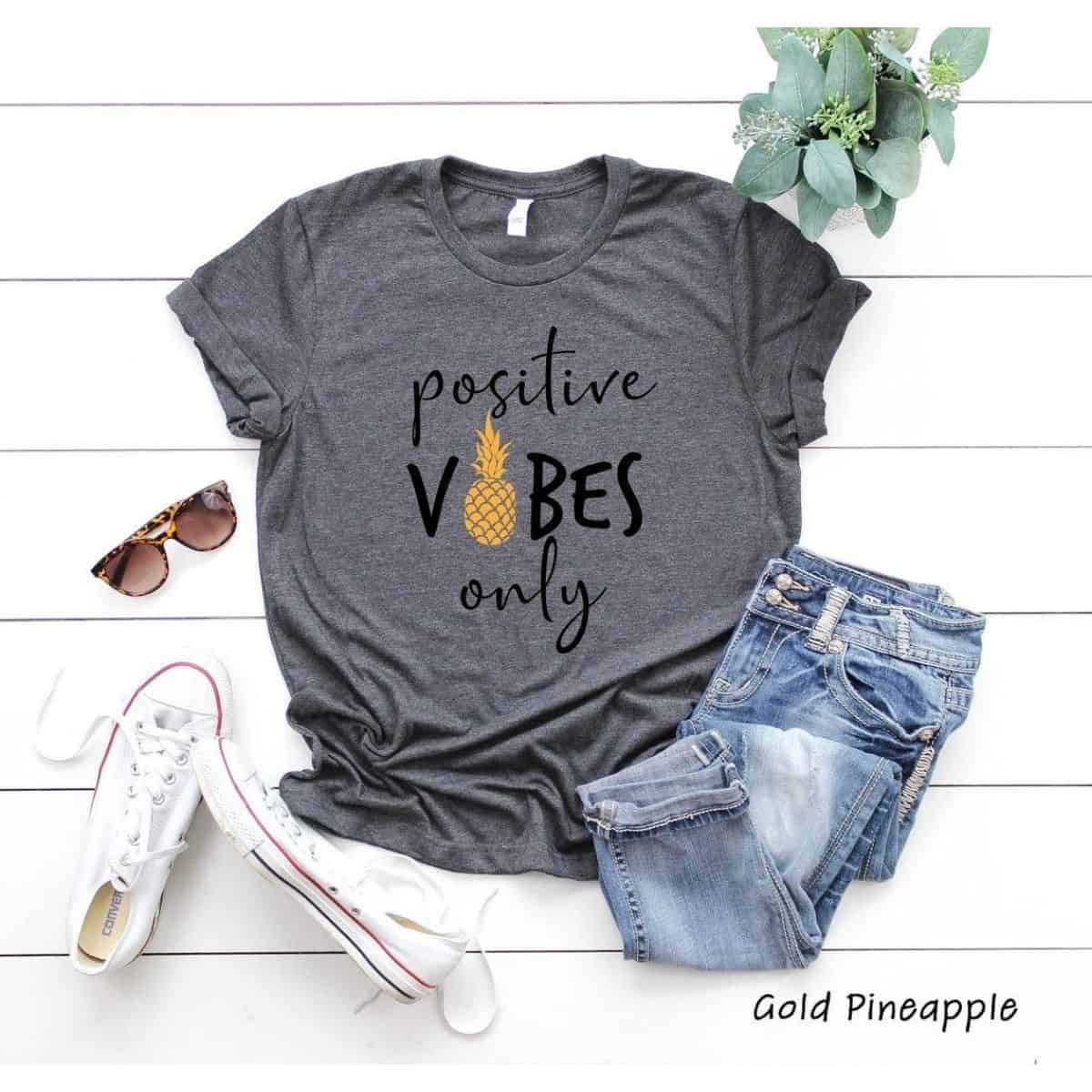 """a gray t-shirt that reads """"positive vibes only"""" with a yellow pineapple"""