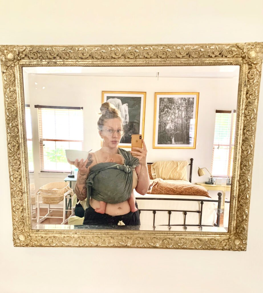 Rachel taking a mirror selfie while holding her newborn son in a swaddle