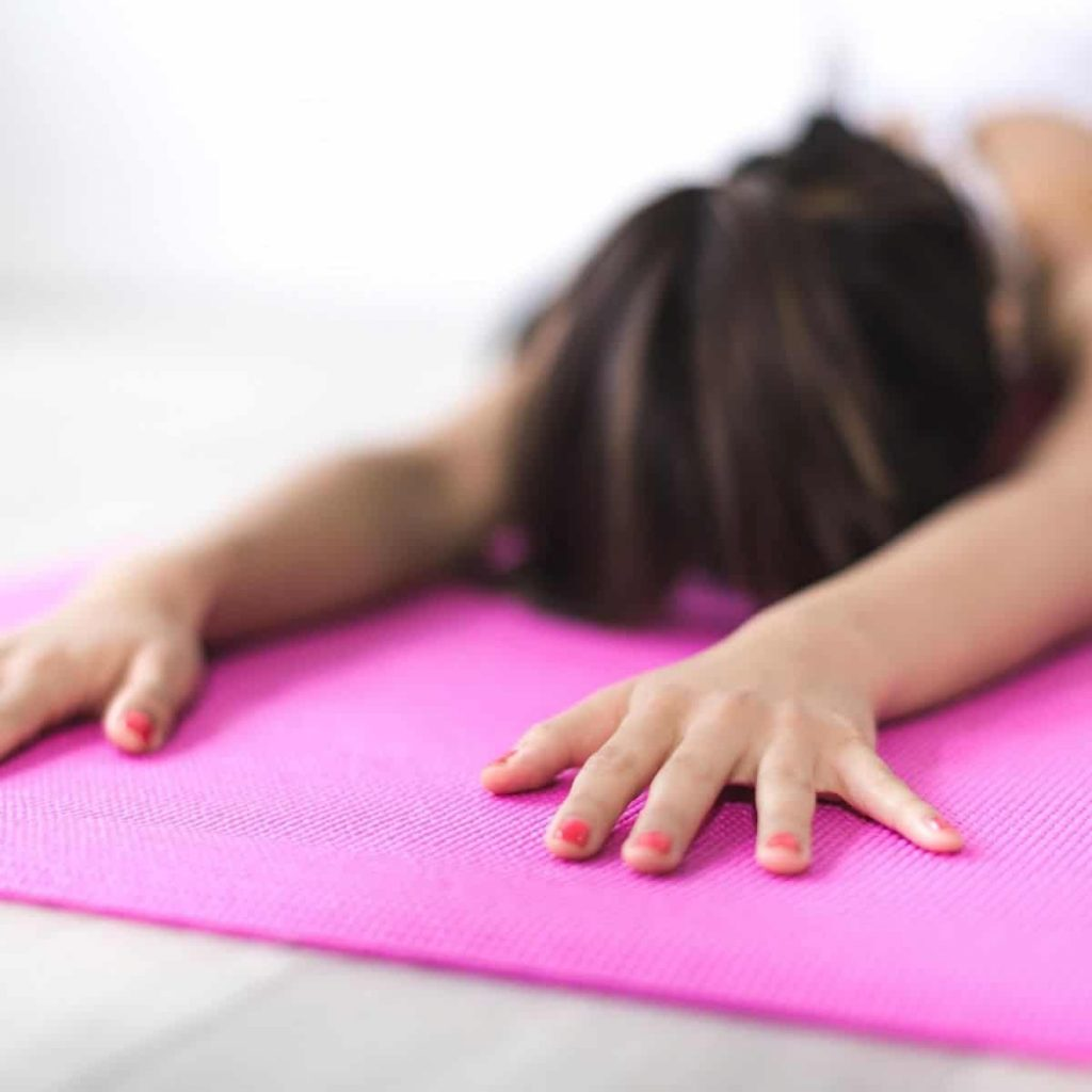 woman is stretching on a pink yoga mat