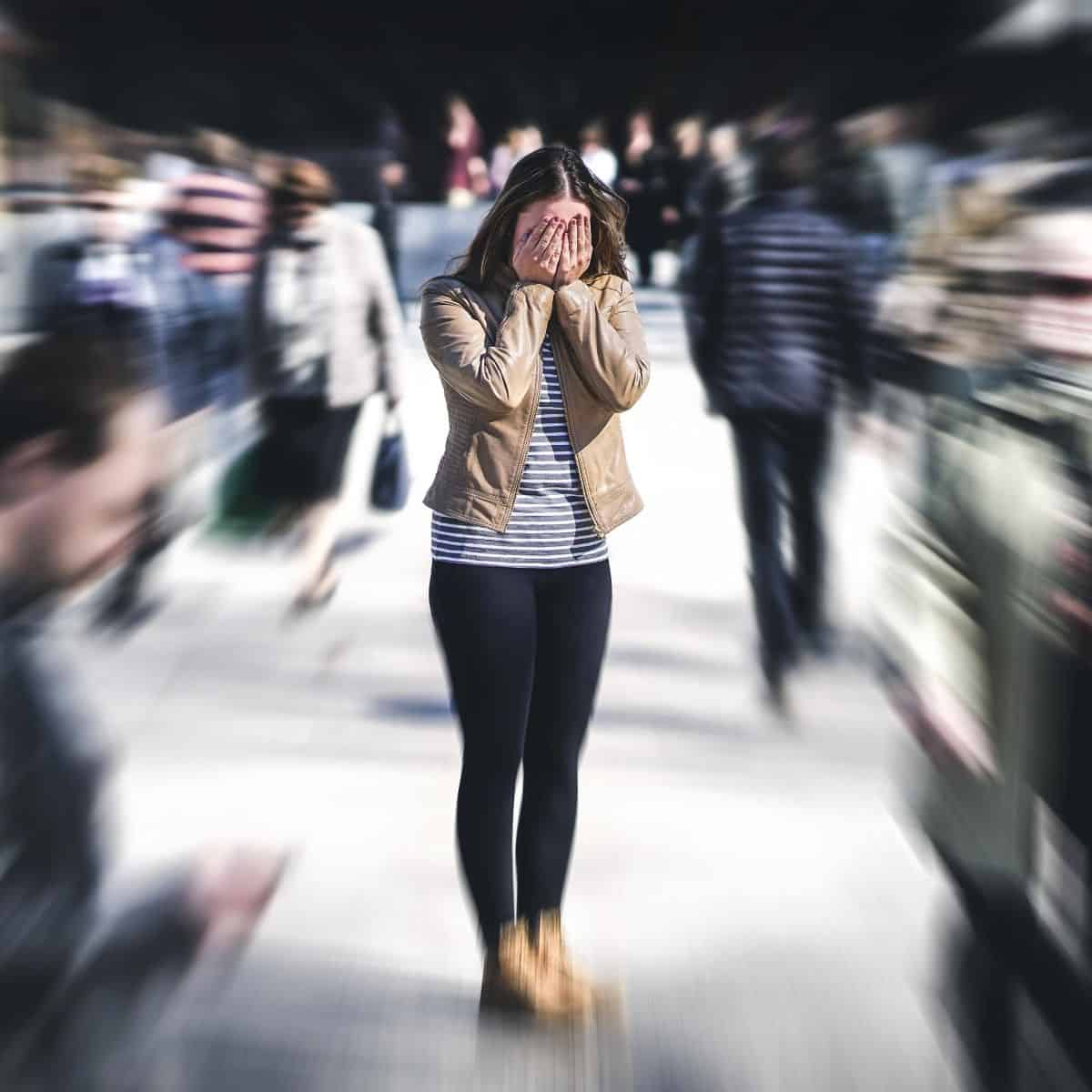 young woman is the focus in the middle of a crowded sidewalk while she hides her face in her hands
