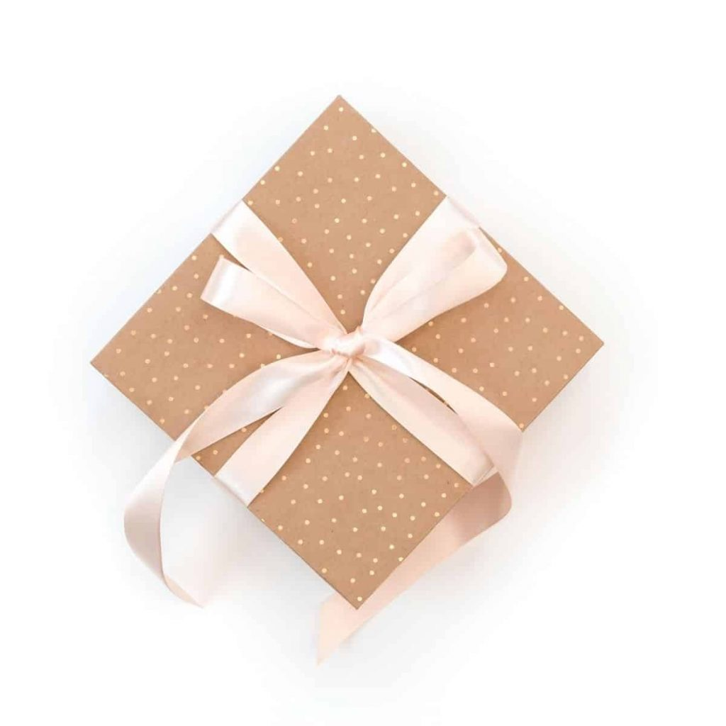 a polka dot gift box with pink ribbon wrapped around it