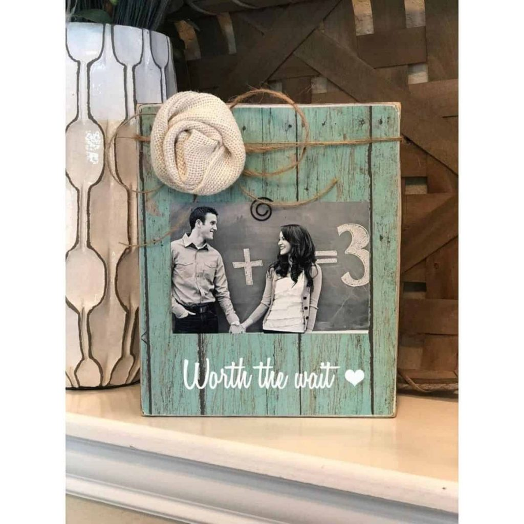 "green photo frame that shows a pregnant couple holding hands with text that reads ""worth the wait"""