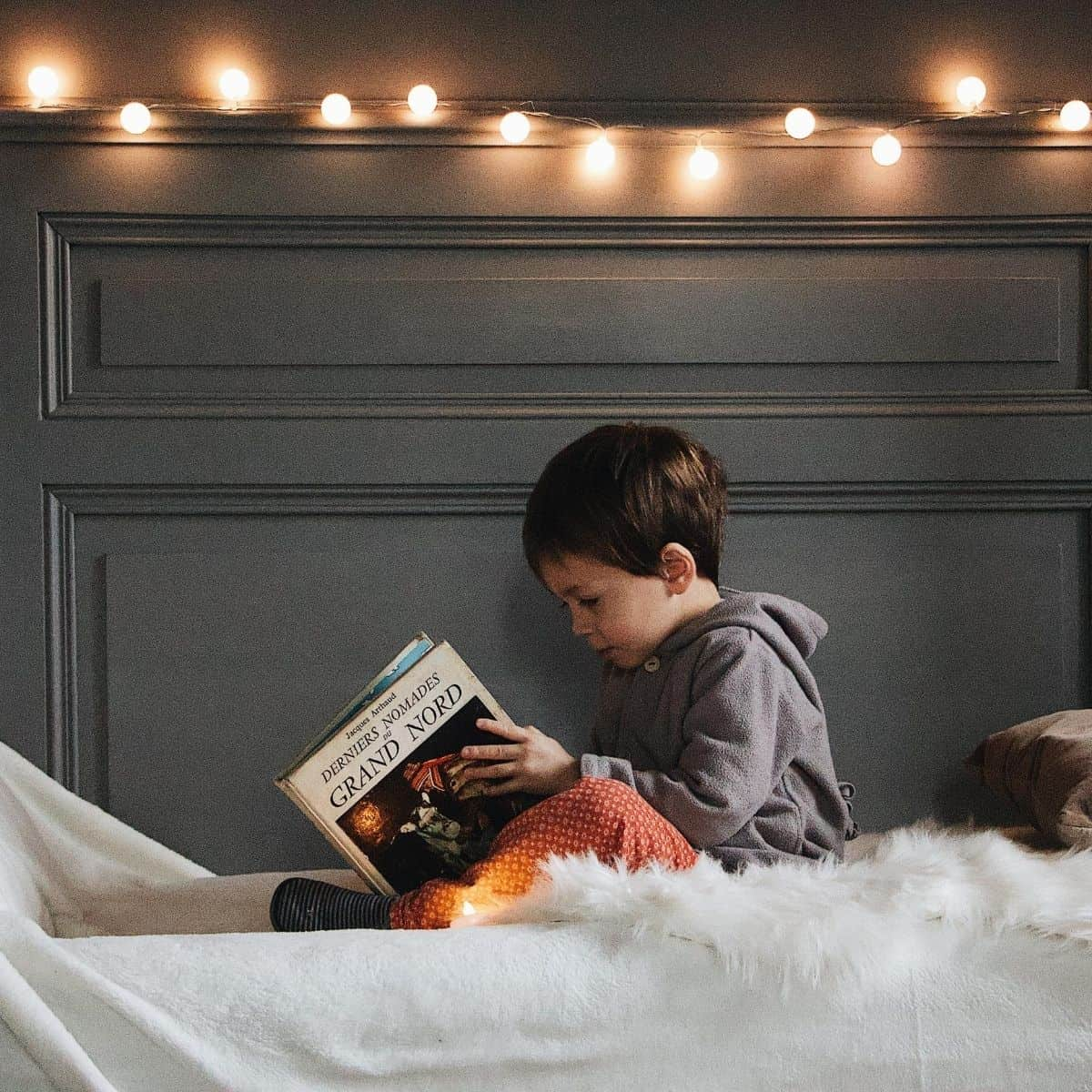Toddler is reading a book while in bed with nightlights spread out on headboard