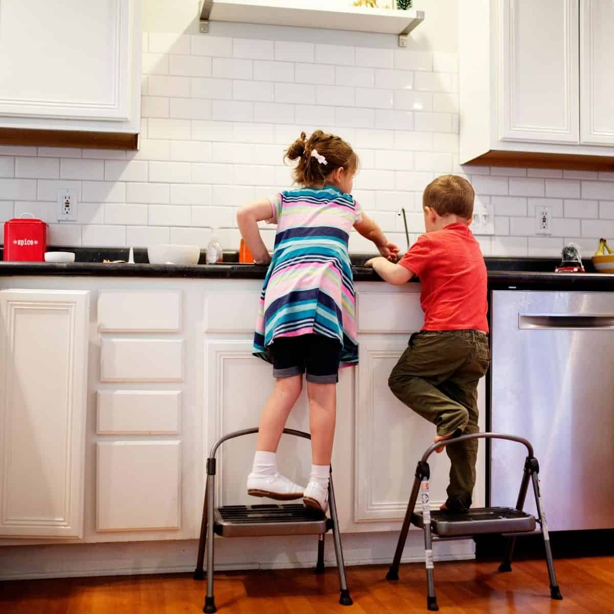 boy and girl standing on stepping tools in front of kitchen sink to do the dishes