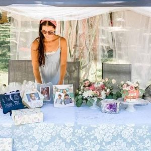 woman standing behind outdoor table with decorations and a cake for baby shower