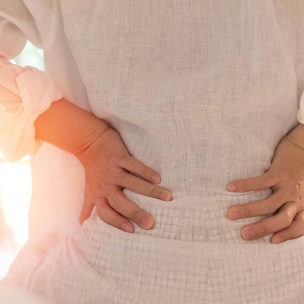 backside of a woman's lower back with hands holding it in pain