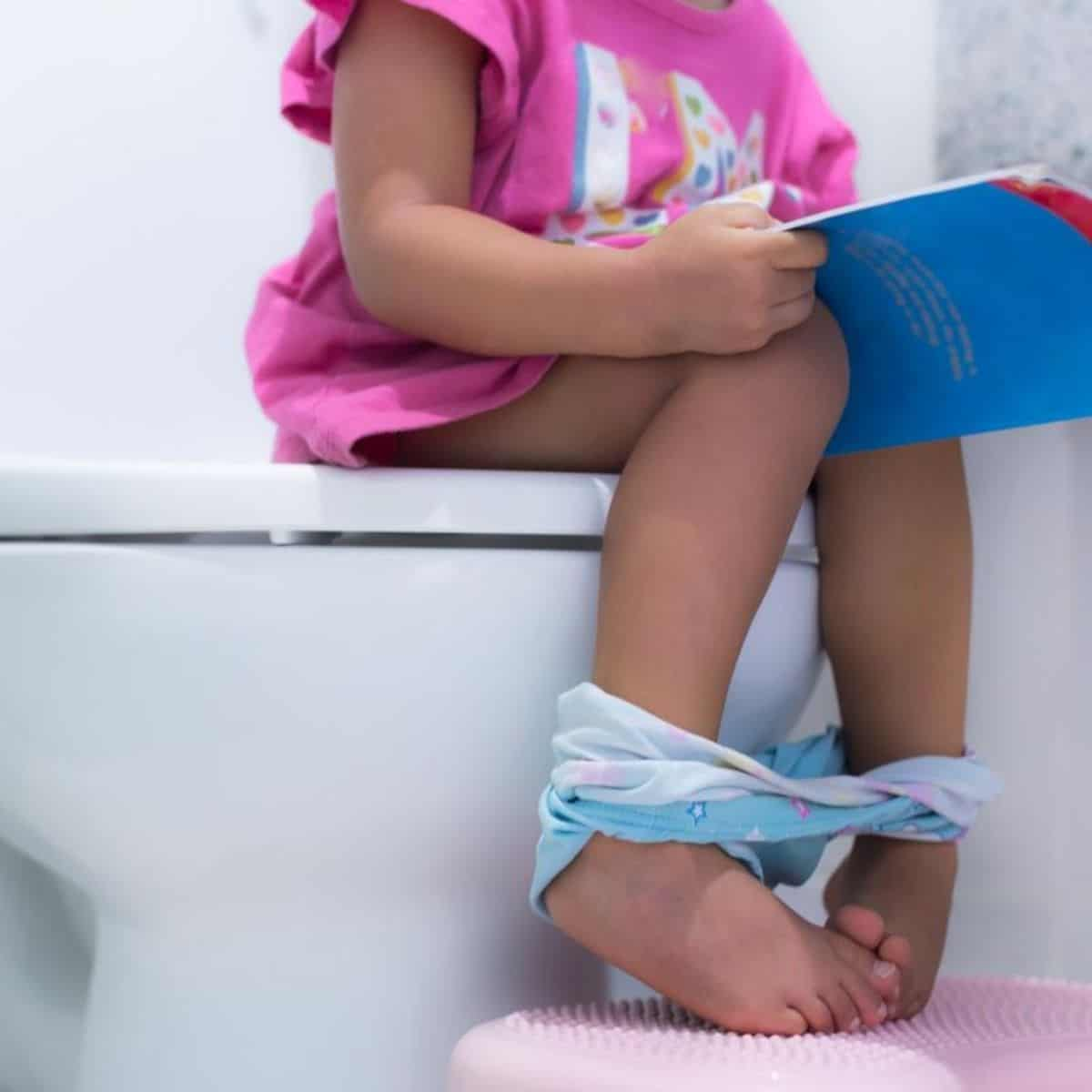 little girl is sitting on a toilet with a book in her hands