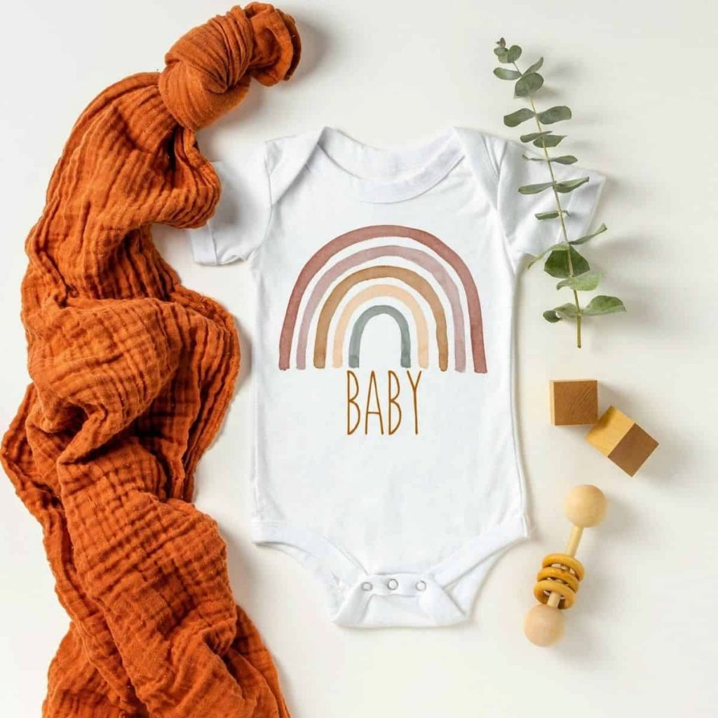 flatlay photo of a onesie with a dark colored rainbow that says baby underneath