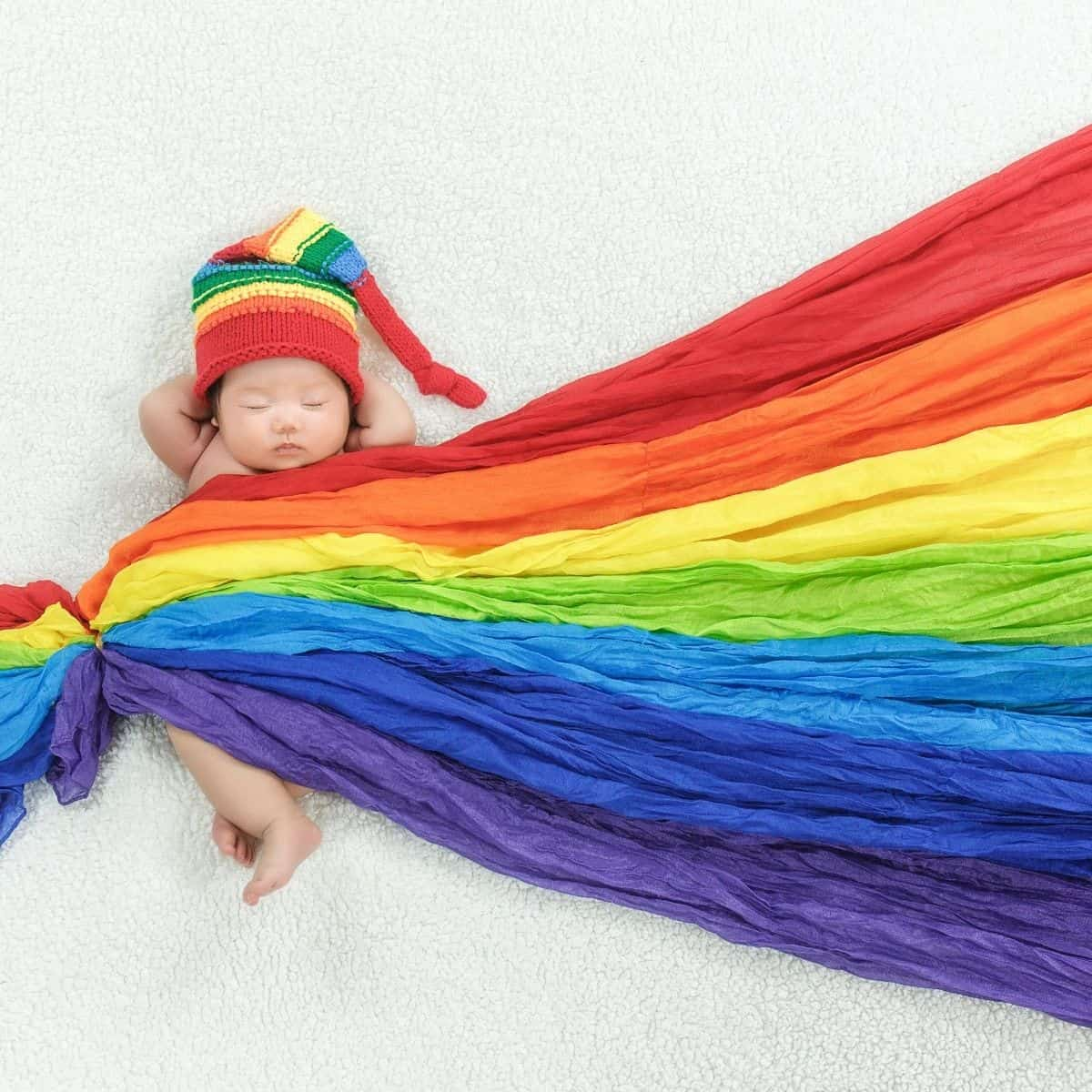 infant wearing a rainbow colored hat and wrapped in rainbow blanket