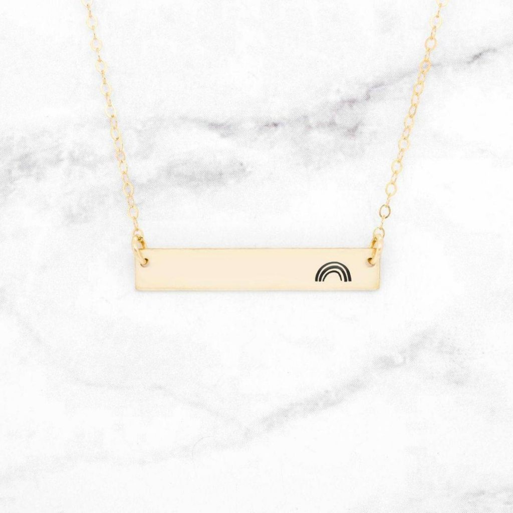 golden necklace with a rainbow outline painted on it