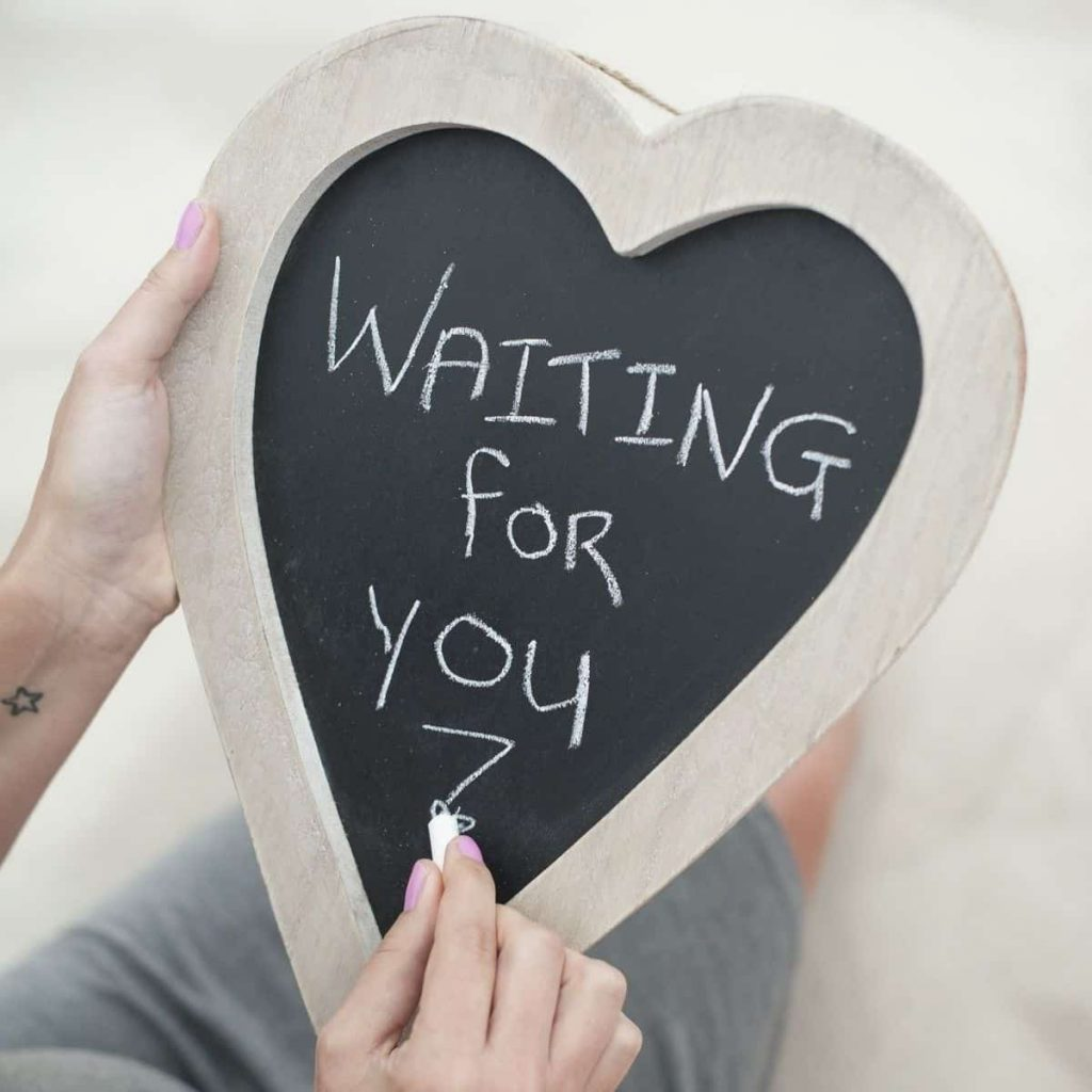 "heart shaped chalkboard with someone writing ""waiting for you"""