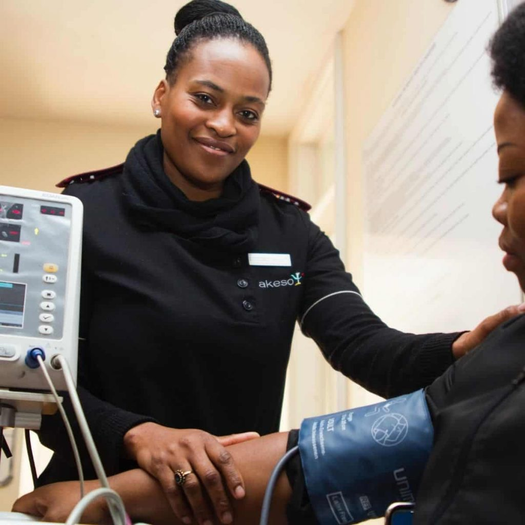 women is smiling while checking blood pressure on a patient