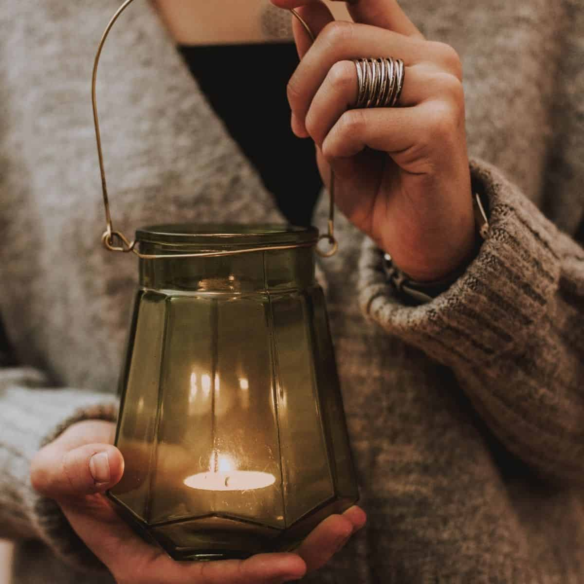 hands holding candle lamp