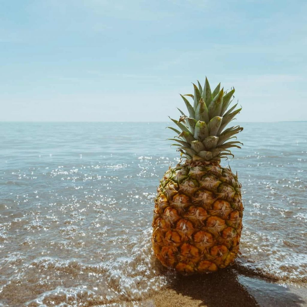 pineapple on the beach with ocean water approaching
