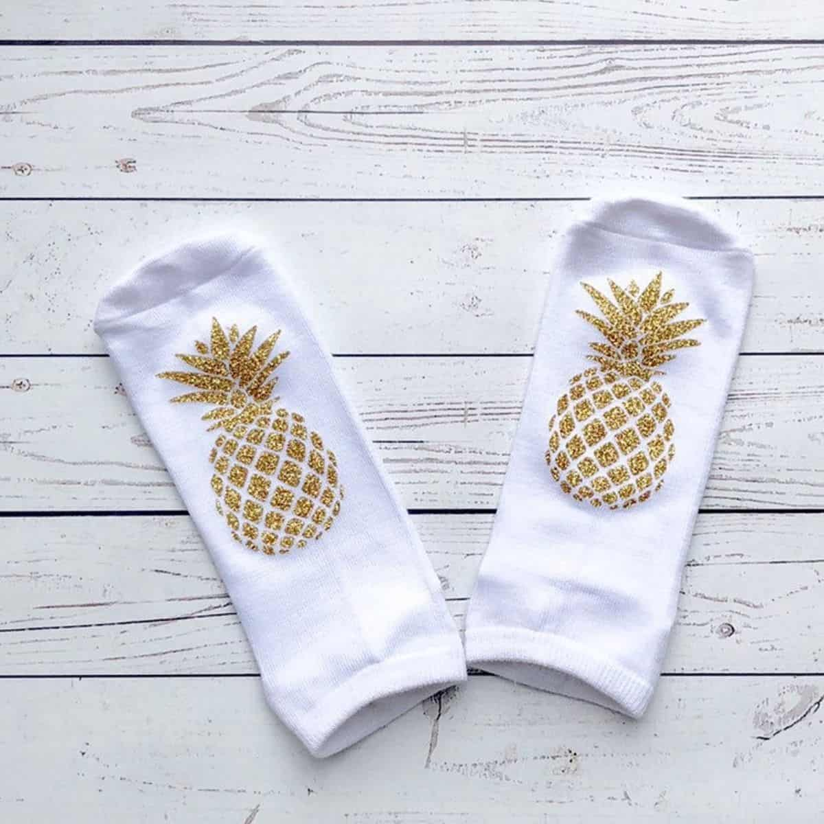 pair of white socks with sparkly gold pineapples