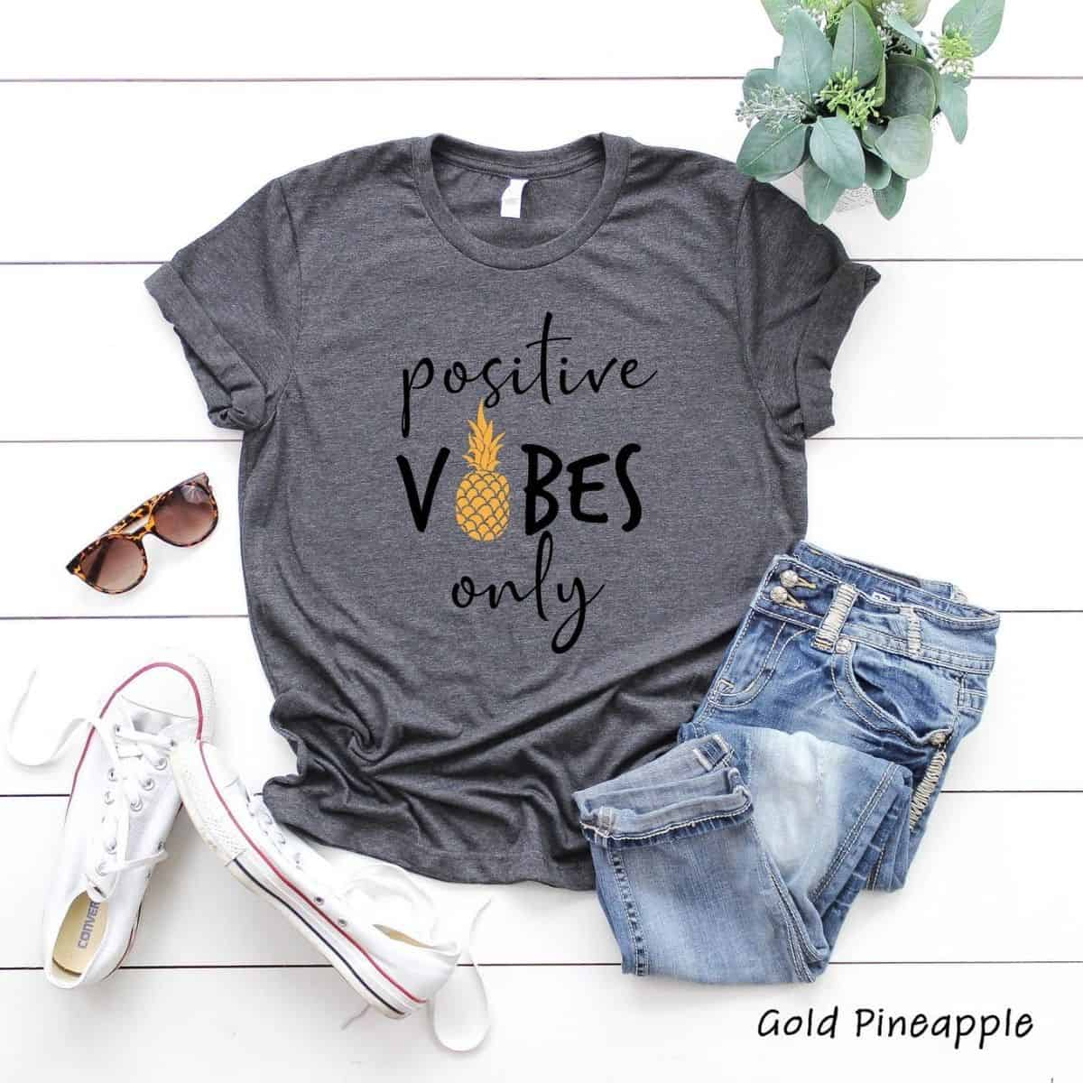 gray tshirt laid out with a pair of jeans, sunglasses, and white sneakers