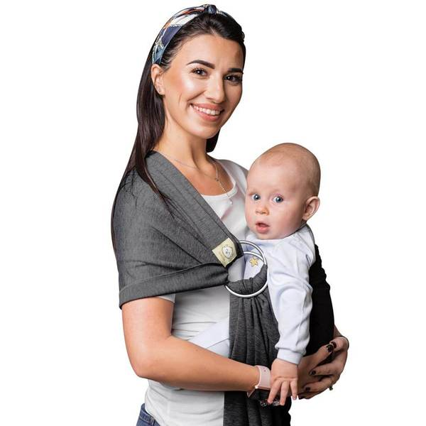 mom smiling at camera while wearing baby in a ring sling